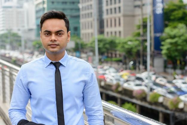 Portret van jonge knappe indiase zakenman in de stad