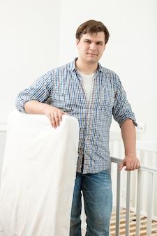 Portret van jonge knappe man die zich voordeed op babybedje met nieuwe matras