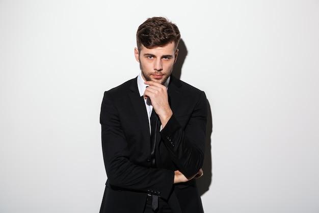 Portret van jonge knappe man in zwart pak met zijn kin