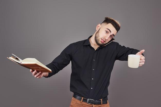 Portret van jonge knappe man met telefoon, kopje koffie en boek over handen.