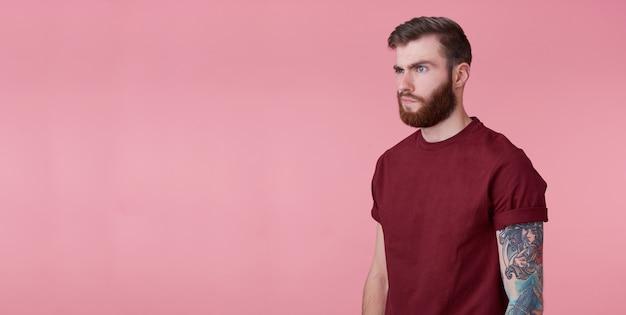 Portret van jonge knappe misverstand rode bebaarde man in rood t-shirt, staat op roze achtergrond, lijkt ruimte aan de linkerkant te kopiëren, staat op roze achtergrond.