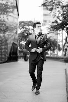 Portret van jonge knappe spaanse zakenman buiten het kantoorgebouw in zwart-wit