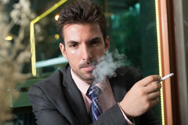 Portret van jonge knappe spaanse zakenman in pak bij de koffieshop