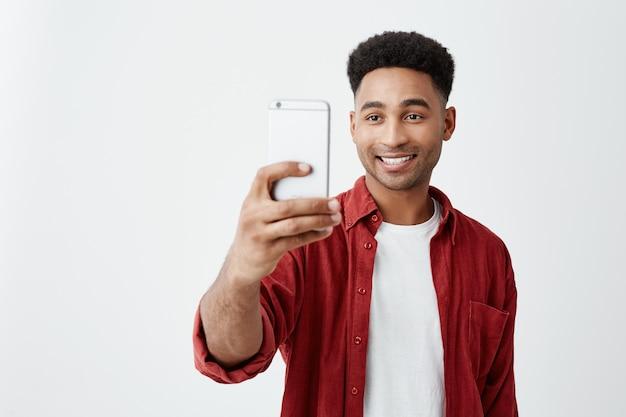Portret van jonge knappe tan-gevilde amerikaanse man met afro kapsel in casual modieuze outfit lachend met tanden, foto van vrienden tijdens vakantie.