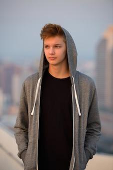 Portret van jonge knappe tiener tegen mening van de stad in openlucht