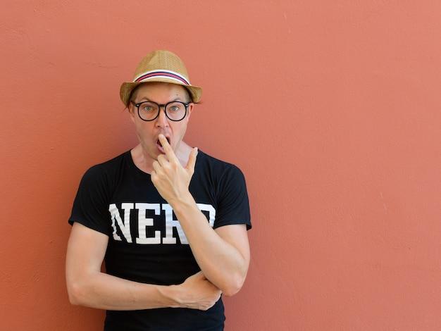 Portret van jonge knappe toeristenmens als nerd tegen gekleurde achtergrond buitenshuis
