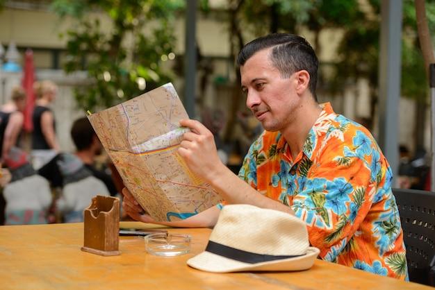 Portret van jonge knappe toeristische man in restaurant in de stad buitenshuis