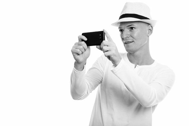 Portret van jonge knappe toeristische man met hoed geïsoleerd op wit in zwart-wit