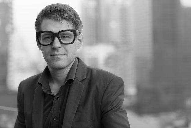 Portret van jonge knappe zakenman in pak tegen uitzicht over de stad in zwart-wit