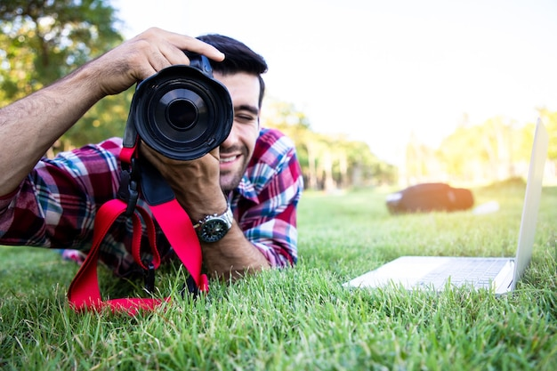 Portret van jonge knappe zakenman met behulp van dslr digitale camera en maak een foto met natuurlijke op openbaar park