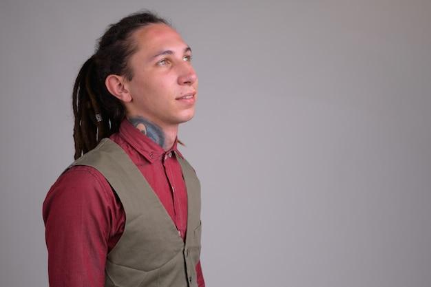 Portret van jonge knappe zakenman met dreadlocks tegen witte muur