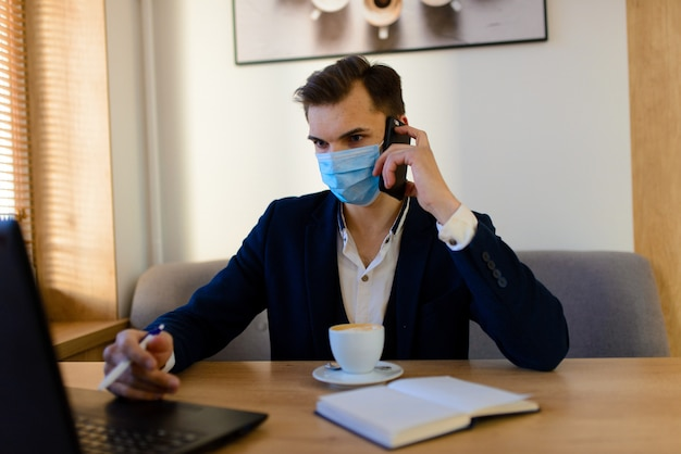 Portret van jonge knappe zakenman met gezichtsmasker in quarantaine van griep. foto in cafe met laptop, mobiele telefoon.