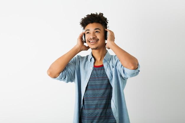 Portret van jonge knappe zwarte man, luisteren naar muziek op koptelefoon op wit