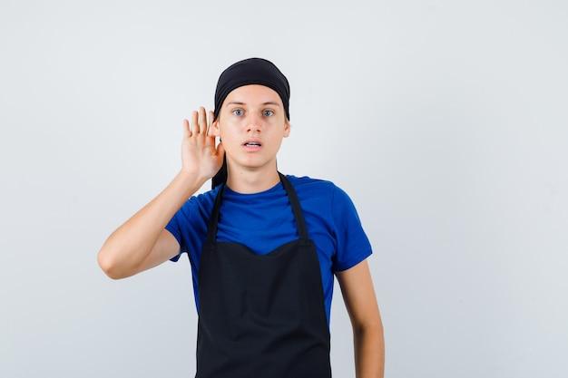Portret van jonge kok man met hand achter oor in t-shirt, schort en serieus vooraanzicht