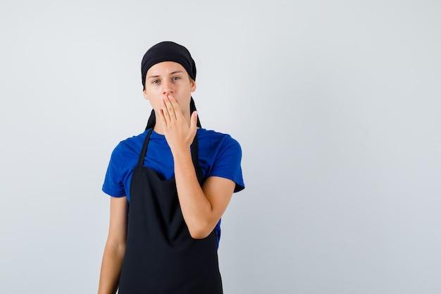 Portret van jonge kok man met hand op mond in t-shirt, schort en verbaasd vooraanzicht