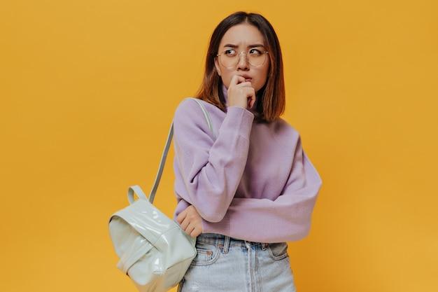Portret van jonge kortharige vrouw in bril, paarse trui ziet er attent uit en poseert met mintrugzak op geïsoleerde muur