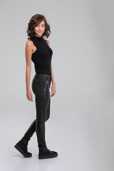 Portret van jonge krullende mooie vrouw in zwarte kleren die zich op witte muur bevinden