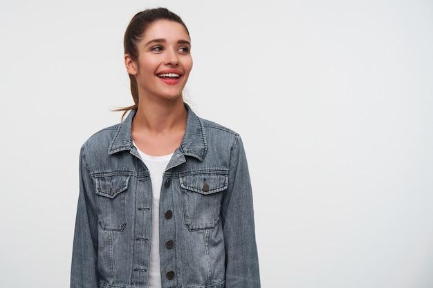 Portret van jonge lachende brunette dame draagt in wit t-shirt en spijkerjasjes, kijkt weg met gelukkige uitdrukking, staat op witte achtergrond met kopie ruimte aan de rechterkant.