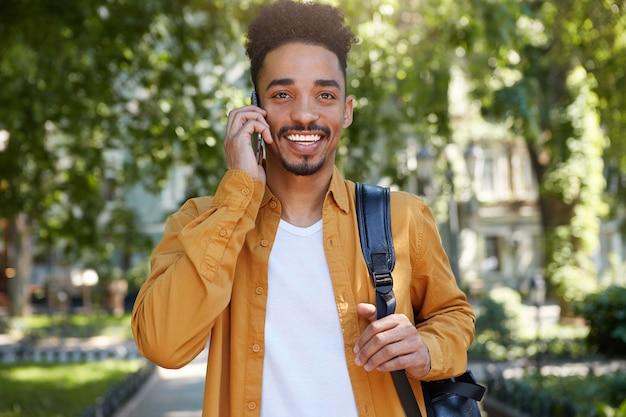 Portret van jonge lachende donkere student man in geel overhemd, wandelen in het park, spreken op smartphone met zijn vriend, wegkijken en genieten van de dag.