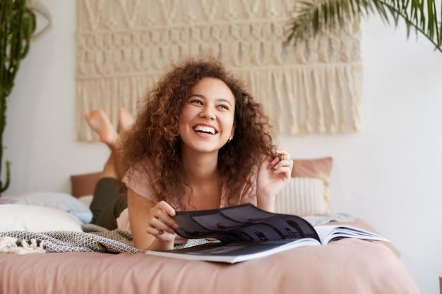 Portret van jonge lachende donkere vrouw met krullend haar, ligt op het bed en leest een tijdschrift, geniet van zonnige vrije dag, kijkt weg en glimlacht breed.