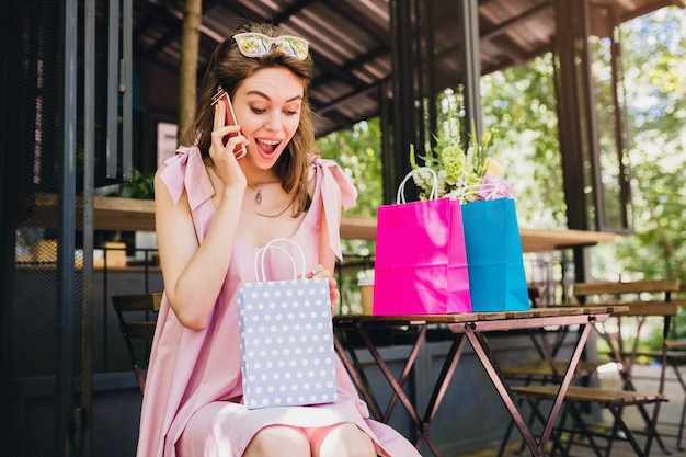 Portret van jonge lachende gelukkig aantrekkelijke vrouw zitten in café praten over de telefoon met boodschappentassen, zomer mode outfit, hipster stijl, roze katoenen jurk, verbaasd gezicht