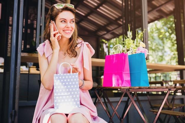 Portret van jonge lachende gelukkig aantrekkelijke vrouw zitten in café praten over telefoon met boodschappentassen, zomer mode outfit, hipster stijl, roze katoenen jurk, trendy kleding