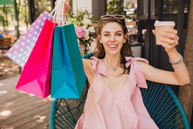 Portret van jonge lachende gelukkig mooie vrouw met opgewonden gezicht expressie zitten in café met boodschappentassen koffie drinken, zomer mode outfit, roze katoenen jurk, trendy kleding