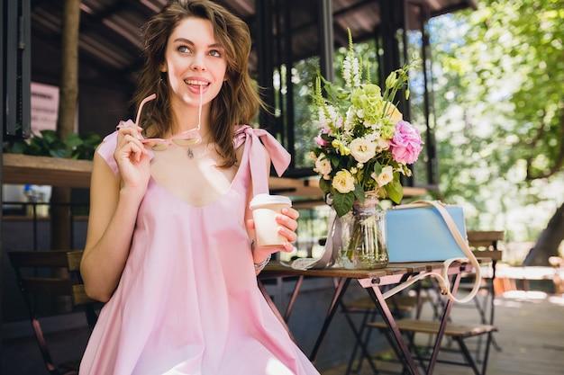 Portret van jonge lachende gelukkig mooie vrouw met zittend in café koffie drinken, zomer mode outfit, hipster stijl, roze katoenen jurk, trendy kledingaccessoires