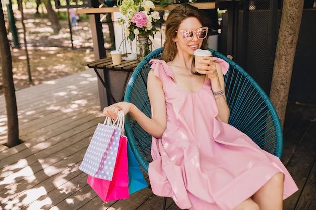 Portret van jonge lachende gelukkig mooie vrouw zitten in café met boodschappentassen drinken koffie, zomer mode outfit, roze katoenen jurk, trendy kleding