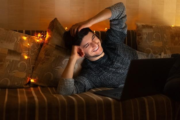 Portret van jonge lachende man liggend op de bank, kijken in laptop