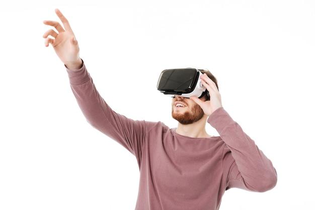 Portret van jonge lachende man met behulp van virtual reality-bril en zijn hand opdagen