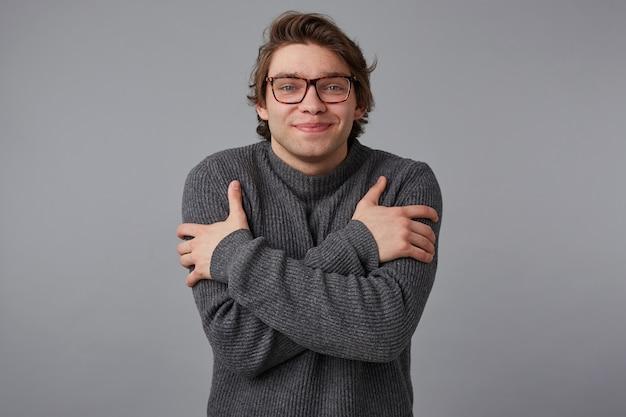 Portret van jonge lachende man met bril draagt in grijze trui, staat over grijze achtergrond en knuffelt zichzelf, ziet er happines uit.