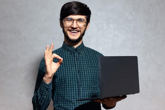 Portret van jonge lachende man met laptop in handen