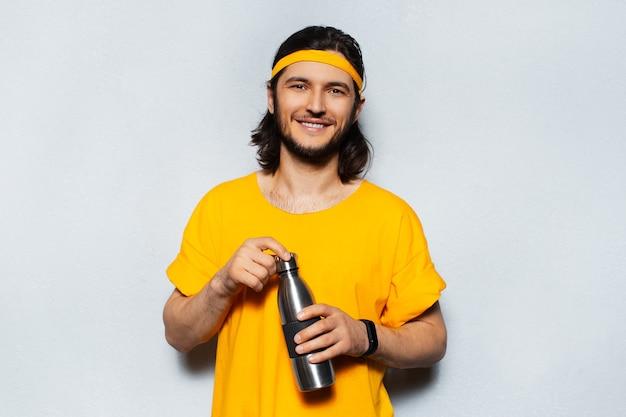 Portret van jonge lachende man met oranje t-stuk met een aluminium fles op witte achtergrond white