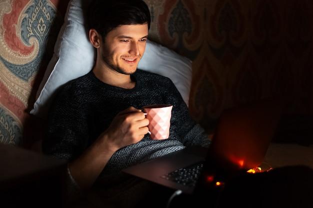 Portret van jonge lachende man thuis werken op laptop in de nacht kamer