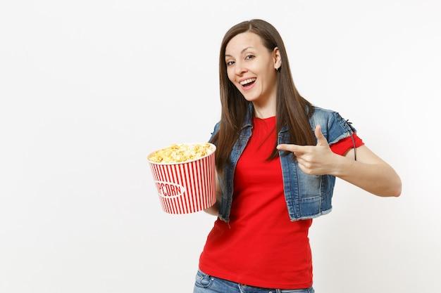Portret van jonge lachende mooie brunette vrouw in casual kleding kijken naar film film, wijzende wijsvinger houden op emmer popcorn geïsoleerd op een witte achtergrond. emoties in bioscoopconcept.