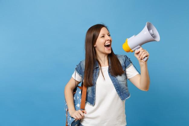 Portret van jonge lachende mooie vrouw student in denim kleding met rugzak maken aankondiging met megafoon geïsoleerd op blauwe achtergrond. onderwijs op de middelbare school. kopieer ruimte voor advertentie.