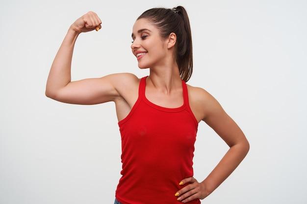 Portret van jonge lachende schattige brunette vrouw draagt in rood t-shirt toont een beceps en uitstekende fitness vorm. staat op een witte achtergrond.