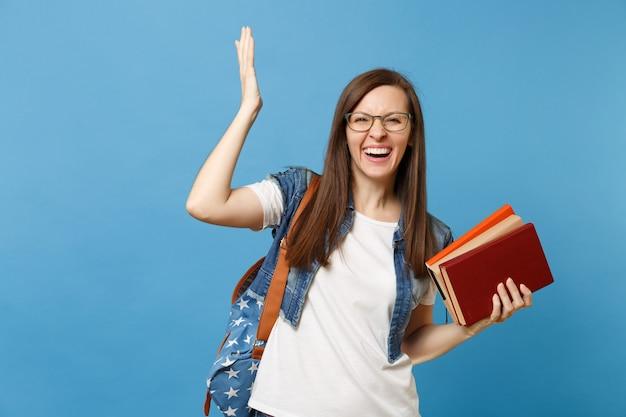 Portret van jonge lachende schattige vrouw student in glazen met rugzak verspreiding verhogen hand omhoog houden schoolboeken geïsoleerd op blauwe achtergrond. onderwijs in het concept van de middelbare schooluniversiteit.
