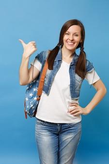 Portret van jonge lachende vrolijke gelukkige vrouw student in wit t-shirt, denim kleding met rugzak wijzende duim opzij geïsoleerd op blauwe achtergrond. onderwijs op de universiteit. kopieer ruimte voor advertentie.