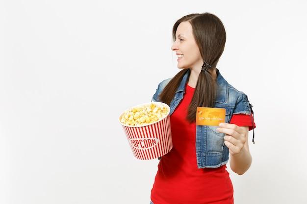 Portret van jonge lachende vrouw in casual kleding kijken naar film film, emmer popcorn en creditcard vasthouden, opzij kijken op kopie ruimte geïsoleerd op een witte achtergrond. emoties in bioscoopconcept.
