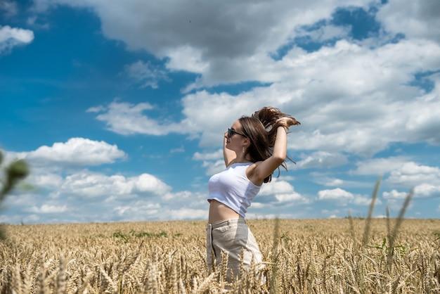 Portret van jonge lachende vrouw in een tarweveld. gratis gelukkig meisje