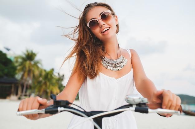 Portret van jonge lachende vrouw in witte jurk rijden op tropisch strand op fiets zonnebril reizen op zomervakantie in thailand close-up
