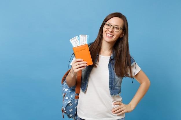 Portret van jonge lachende vrouw student in glazen met rugzak met paspoort, instapkaart tickets geïsoleerd op blauwe achtergrond. onderwijs aan hogeschool in het buitenland. vliegreis vlucht concept.