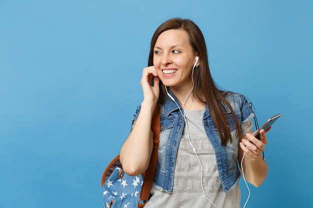 Portret van jonge lachende vrouw student met rugzak, koptelefoon luisteren muziek met mobiele telefoon opzij kijken geïsoleerd op blauwe achtergrond. onderwijs aan de universiteit. kopieer ruimte voor advertentie.