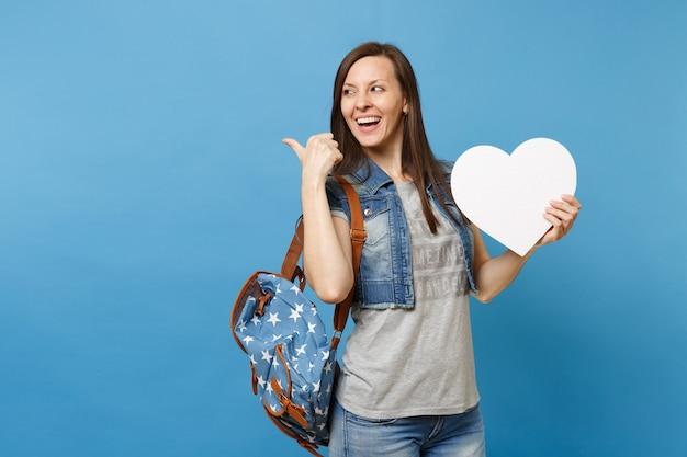 Portret van jonge lachende vrouw student met rugzak met wit hart met kopie ruimte wijzende duim opzij geïsoleerd op blauwe achtergrond. onderwijs op de middelbare school. kopieer ruimte voor advertentie.