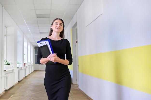 Portret van jonge lachende vrouwelijke leraar op school. vrouw in zwarte jurk met map, digitale tablet wandelen langs gang