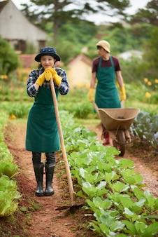 Portret van jonge landbouwer die met gravende schoffel camera met haar collega bekijken die de wagen duwen bij de achtergrond