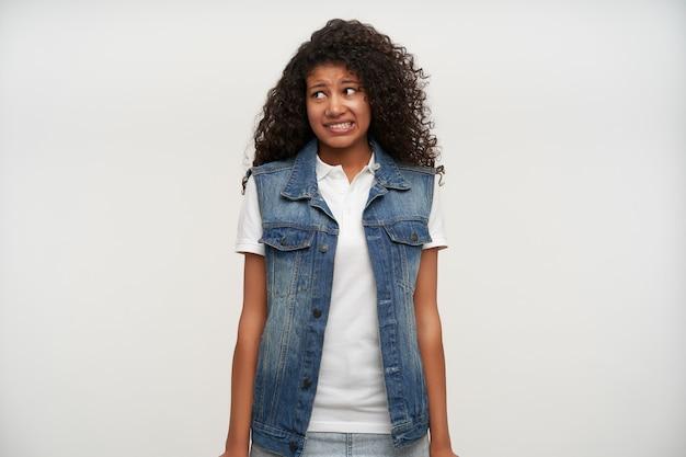 Portret van jonge langharige brunette krullende vrouw met donkere huid opzij kijken met oeps gezicht en toont haar perfecte witte tanden, geïsoleerd op wit