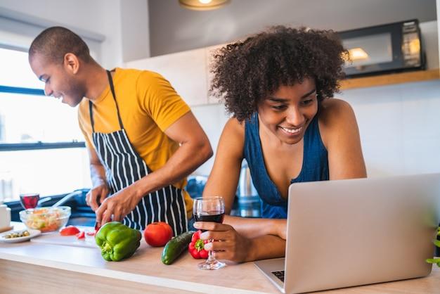 Portret van jonge latijns-paar met behulp van een laptop tijdens het koken in de keuken thuis. relatie-, kook- en levensstijlconcept.